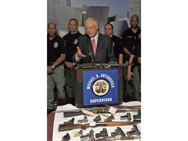 Supervisor Michael D. Antonovich points to a display of weapons during a news conference Monday. Antonovich initiated the D.I.S.A.R.M. program in response to the August 1999 shootings at the North Valley Jewish Community Center in Granada Hills.