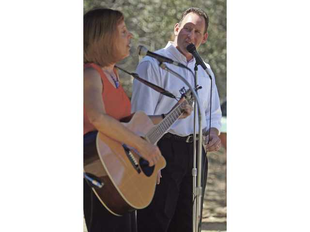 Rabbi Mark Blazer, right, sings with Wendy Hersh at the 10-year anniversary of the North Valley Jewish Community Center shooting Monday morning.