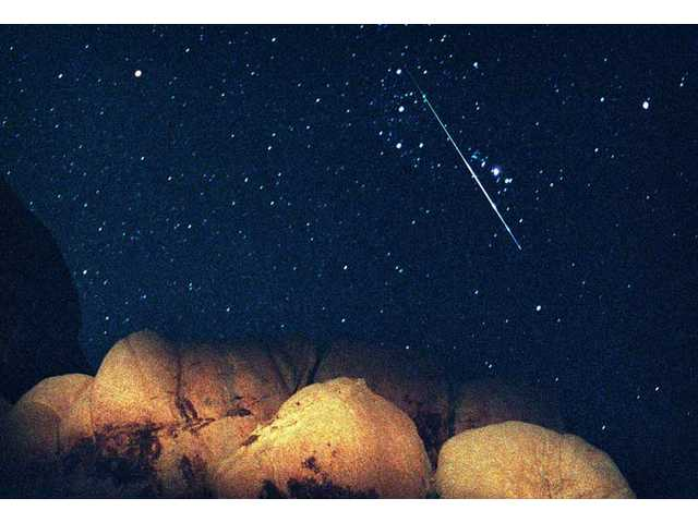 In this Aug. 12, 1997 file picture, a bright Perseid Meteor cuts across Orion's Belt during the peak of the annual Perseid Meteor Shower seen from Joshua Tree National Park, Calif. In North America, the best time to watch is before dawn Wednesday, Aug. 12, 2009.