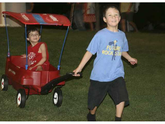As The Craze rock out onstage at Central Park Saturday night, future rock star Noah Faden, 7, of Chatsworth, takes his brother Zander, 5, on a wagon ride downhill.