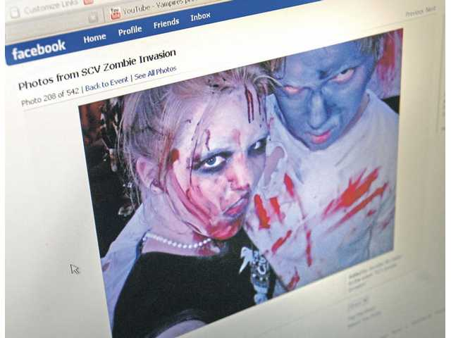 "Dan Watson/The SignalParticipants in the ""SCV Zombie Invasion"" post photos on Facebook, the social networking Web site used to organize the event. Hundreds of teens and 20-somethings dressed up as zombies and walked through Valencia on Monday evening."