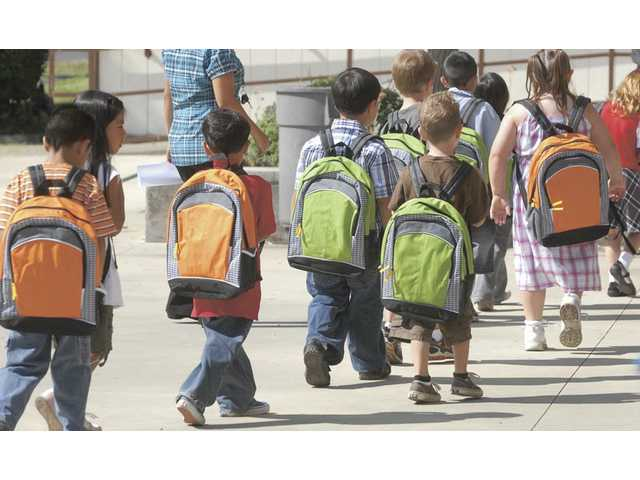 First-graders at Wiley Canyon Elementary School attend their first day of school Wednesday sporting new backpacks they received for free.