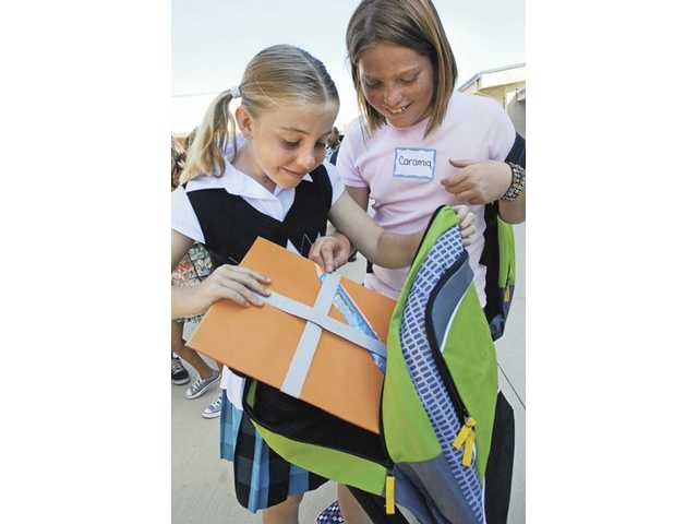 Fifth-graders Cassidy Wilkinson, left, and Caramia Crimi examine the contents of the new backpacks they received for free on Wednesday. Costco Wholesale supplied free back-to-school supplies to more than 760 Wiley Canyon Elementary students as part of the 2009 Fresh Start Backpack Program.