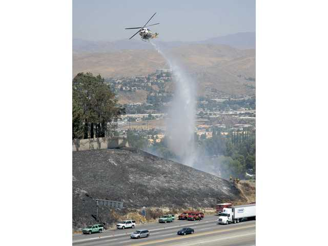 A helicopter makes a drop on a small brushfire near the southbound lanes of Highway 14 freeway near Golden Valley Road on Wednesday.