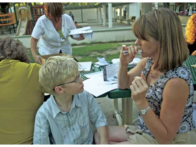 Nine-year-old Adam Solomon watches as his mom Diane Solomon, of Valencia, swabs her mouth to join the Be The Match marrow registry at Valencia Meadows Park on Aug. 7.