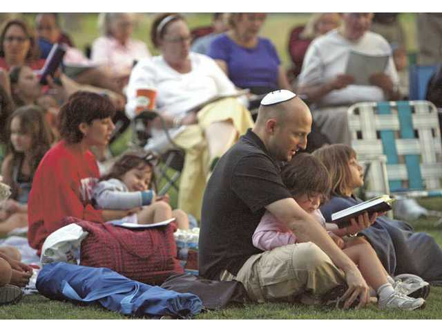 Rob Hershenson reads from the Torah to his 3-year-old daughter, Juliette, as they welcome the Shabbat on Aug. 7 at Valencia Meadows Park.