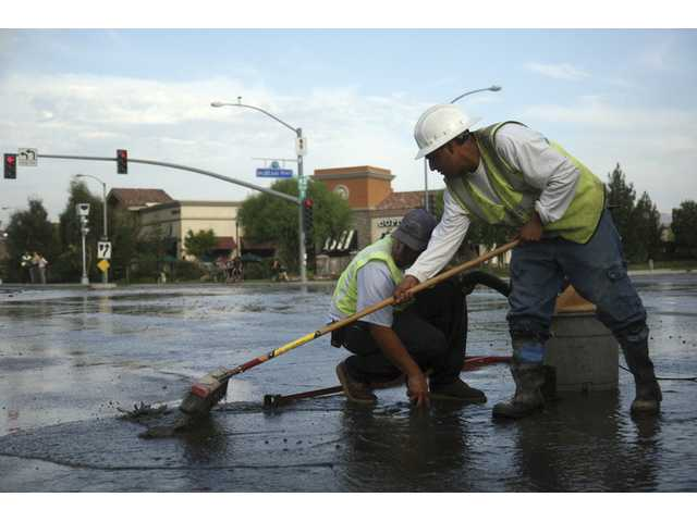 A Valencia Water Company employee works on shutting down a water valve after an underground pipe burst on the corner of Valencia Boulevard and McBean Parkway early Thursday evening. Los Angeles County firefighters, Santa Clarita Valley Sheriff's deputies and Valencia Water Company responded to the scene.