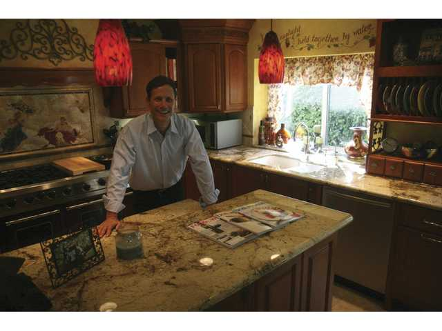 John Dow poses in his European Modern Villa-themed kitchen. The granite countertops are a special junipero granite embedded with quartz and garnet.
