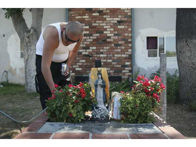 Robert Medrano, 27, from Newhall, waters the flowers on Robert Aguilera Jr.'s sanctuary outside his home, Friday afternoon. Today marks the 10-year anniversary of his brother-in-law's death. Aguilera was 20 years old when he was killed in a drive-by shooting.
