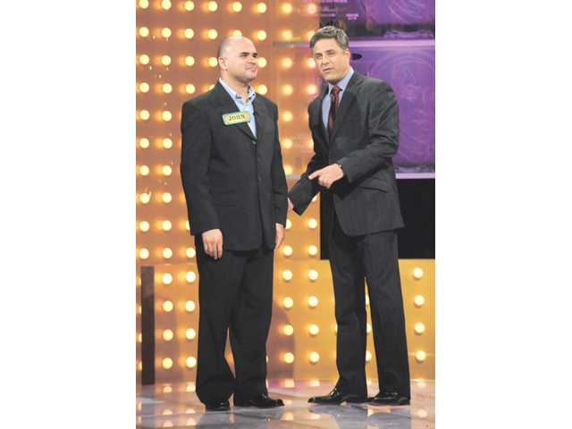 "Canyon Country resident John Pastora, left, stands with game show host Mark Walberg on the set of ""Make Me a Millionaire,"" from the California State Lottery. Pastora won $48,000 on the shows random-play game, ""Safe Cracker."" The show aired Saturday night."