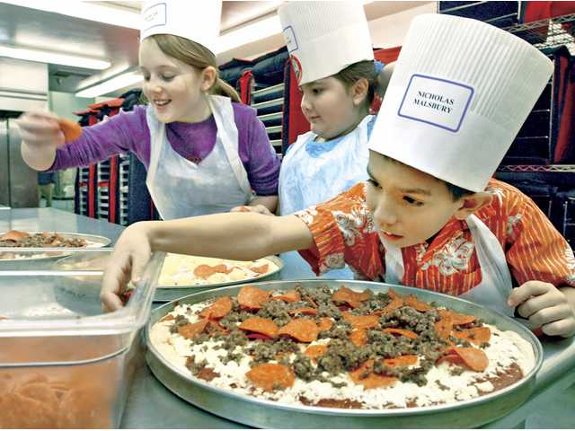 Northlake Hills Elementary fourth-graders Morgan Ries, left, Jenna Rudolph and Nicholas Malsbury make pizzas at the 14th annual Kids Cooking Campaign at Central Kitchen on February 13.