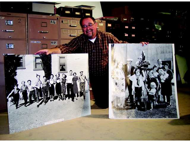 Daniel Watson, of Castaic, holds photos of his famous relatives at the Watson Family Photography Archive in Glendale.