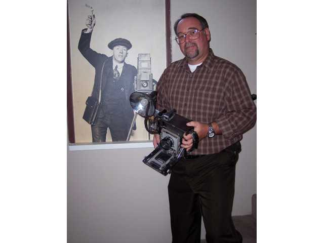 "Daniel Watson stands next to a photo mounted in the lobby of the Watson Family Photography Archive in Glendale of his great-uncle George R. Watson (in 1919). Watson holds an Anniversary model ""Speed Graphic"" - the standard press camera from the 1950s. The camera belonged to Watson's father, Garry Watson."