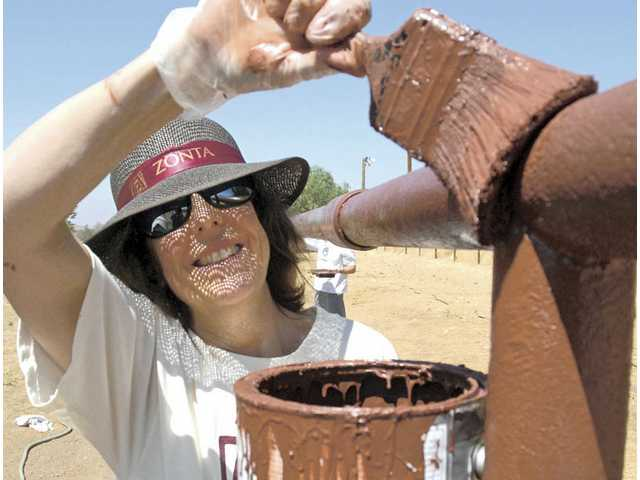 Danise Davis of Zonta Club of SCV makes sure the welds of The Gentle Barn pasture fence rails are covered with paint as she volunteers on Saturday.