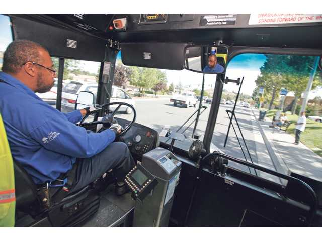 Al Dennis, a Palmdale resident, pulls up to a stop near the intersection of Bouquet Canyon Road and Newhall Ranch Road on Aug. 4. He has been driving Santa Clarita Transit buses for the past 16 years.