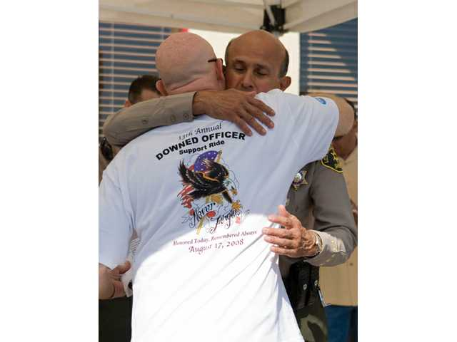 Los Angeles Sheriff's Department Sgt. Tony Arnold embraces Sheriff Lee Baca after the reading of the Downed Officer Roll Call.