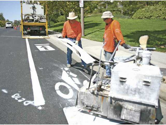 Gene Gonzalez, left, and co-worker Efrain Martinez finish one of the bike path symbols on the corner of Blueridge Drive and Decoro Drive on Tuesday. Decoro Drive, between Seco Canyon Road and McBean Parkway, will have new bike paths on boths sides of the street.