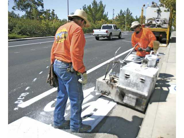 Gene Gonzalez, left, holds a bike-path stencil on the ground as co-worker Efrain Martinez fills it with hot thermal material on the corner of Blueridge Drive and Decoro Drive on Tuesday.