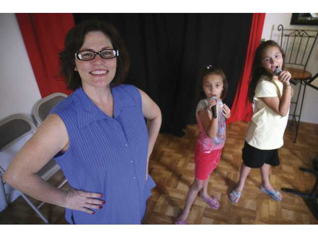 Rene Urbanovich, from Saugus, gives music lessons to two sisters Jolie, 7, and Jasmyn Cadiente, 10, two of her weekly students. Urbanovich teaches singing lessons for young and shy kids.