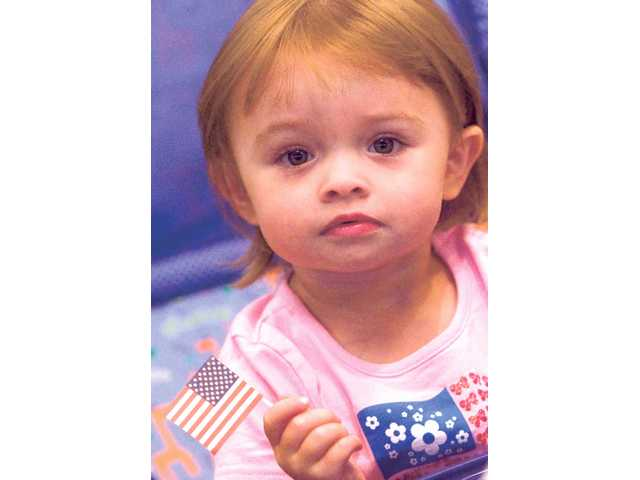 Two-year-old Emma Thorpe waves a tiny American flag as she joined her grandmother Renee Thorpe to a dinner honoring Blue Star Mothers in the SCV.
