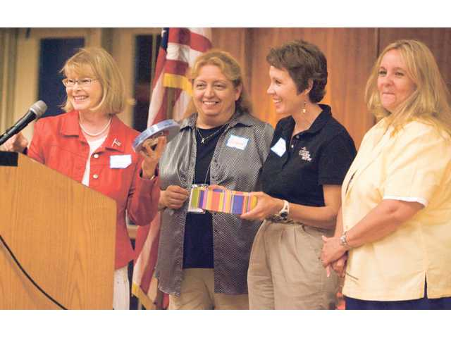 Myrna R. Condie, far left, gives Suzon Gerstel, Kymmer Crookston and Renee Thorpe, representatives of local Blue Star Mother chapters tickets to sell as a fundraiser for each of their chapters.