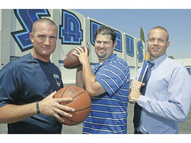 (Left to right) Saugus head football coach Jason Bornn, holding a basketball, baseball head coach John Maggiora, with a football, and basketball head coach Derek Ballard, with a baseball bat, say they have worked together to make sure there are no battles over multi-sport athletes.