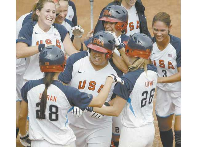 USA softball players surround Crystl Bustos after the Santa Clarita Valley native belted an extra-inning home run to defeat Japan, 4-1.
