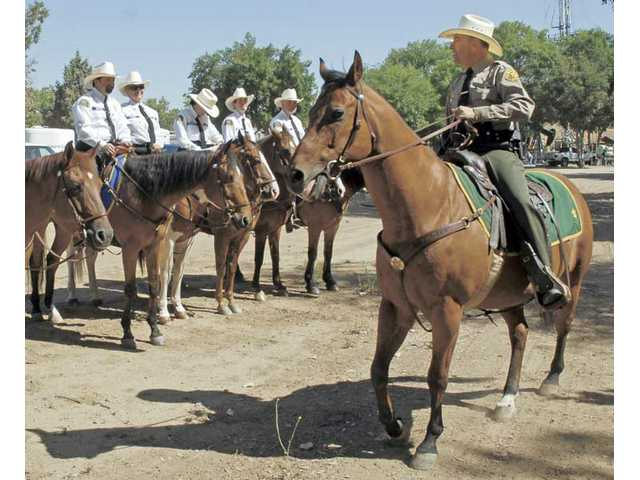 Los Angeles County Sheriff's Captain Tony Pepe, right, on Baron, inspects the mounted members of the posse after the official inspection near Jack Bones Arena in July.
