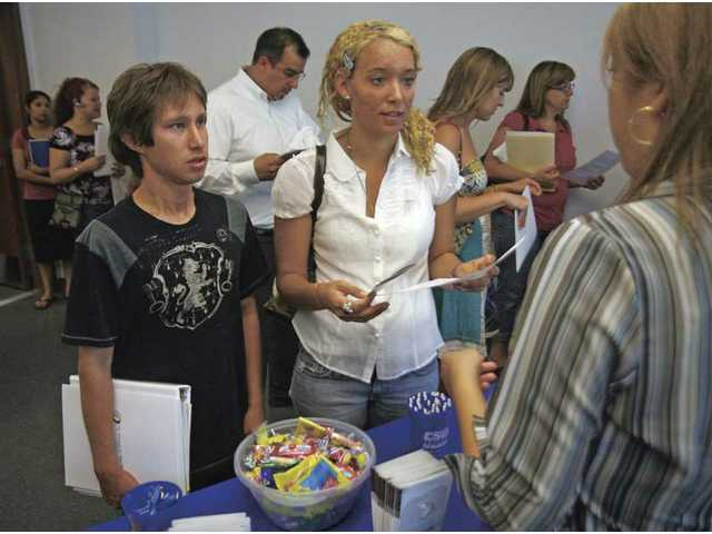 Adrian Burga, 23, left, of Saugus, and Sydney Kincanon, 19, of Canyon Country, get information from California State University representative Liezel Ilarde about their liberal studies program during the University Center's open house on Thursday.