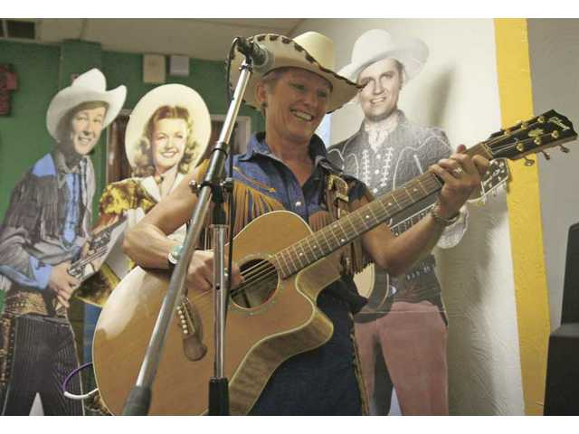 Country singer Joni Harms entertains a small crowd at the OutWest store in downtown Newhall on Friday.