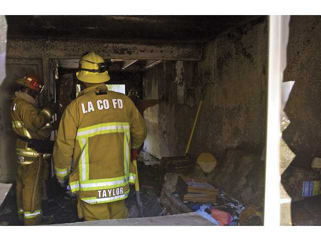 Firefighters from Battalion 6 inspect and clean up after a fire gutted the manager's apartment in Canyon Country.