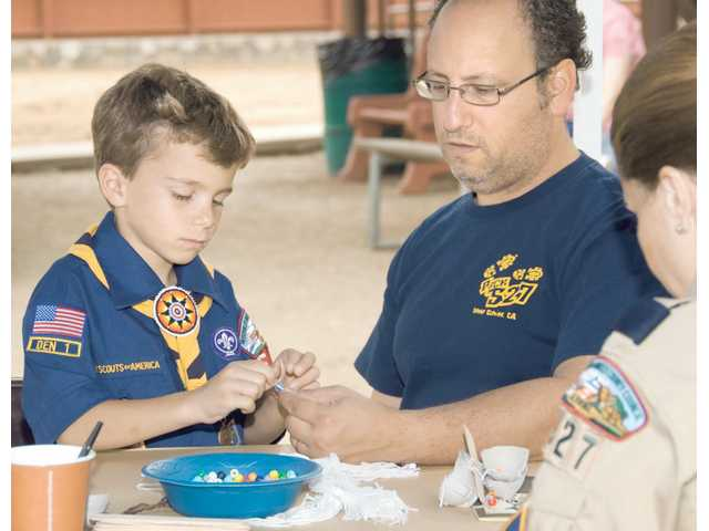 "Michael Rossi, right, helps son Nathan Rossi, 7, learn Native American bead stringing as Wolf Den 1 leader Brenda Elle watches. The hands-on exhibit was part of ""Acorn, Sea and Sage"" day at William S. Hart Park's ""Summer Days at the Ranch,"" a series of educational and fun events designed especially for kids."