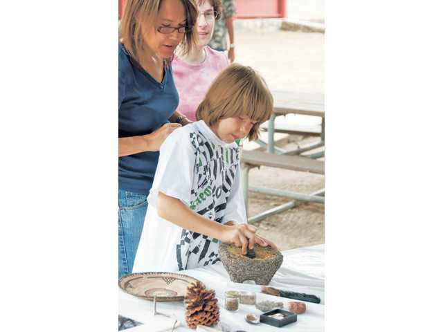 Meadows Elementary student Austin Ketterling, 9, learns how to prepare food as the Chumash Native Americans once did, by smashing acorns, as his mother Jenifer looks on.