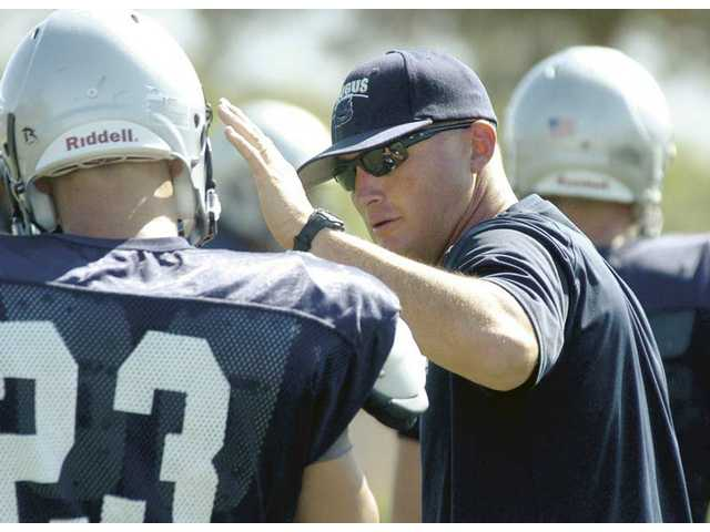 Saugus head football coach Jason Bornn talks with Devin Gustaveson (23) during practice Thursday at Saugus High. With some players complaining of injuries, the Centurions are fighting through early aches and pain as they continue to push toward the season.