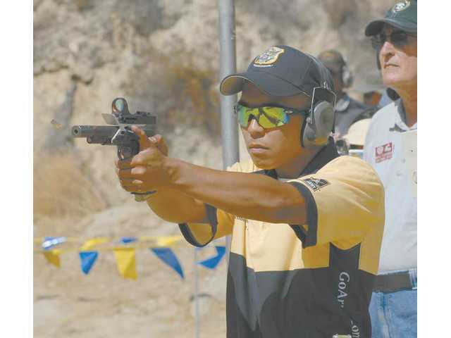 B.J. Norris fires rounds last weekend at the annual Steel Challenge World Speed Shooting championships in Piru. Norris, 19, of East Texas, won the competition and picked up a check for $1,000 to boot.