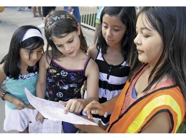 From left, Ariana Almanza, 7, Beth Wagoner, 7, and Janessa Almanza, 9, get directions to their new classrooms from sixth-grader Ashley Curtis, who was acting as a tour guide at Welcome Back Night at Rio Vista Elementary School on Aug. 18.