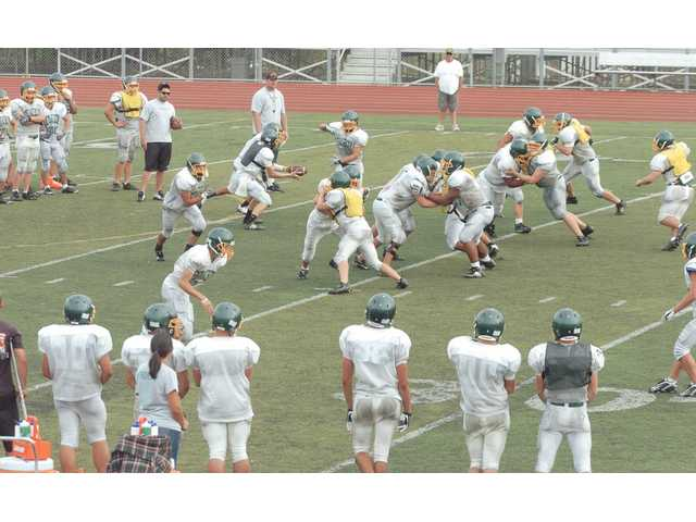 Canyon's offense runs a play against the defense during Friday's practice at Canyon High School.
