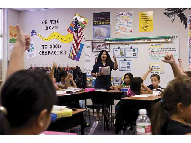Prit Chharba, a new teacher at Emblem Elementary, gives her class the thumbs up while studying language arts.