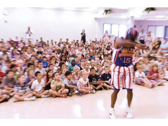 "Buckets Blakes, from the Harlem Globetrotters, shows of some of his moves at North Park Elementary School in Saugus. The Globetrotters showed up at the school to talk to students about their ""C.H.E.E.R. for Character"" program."