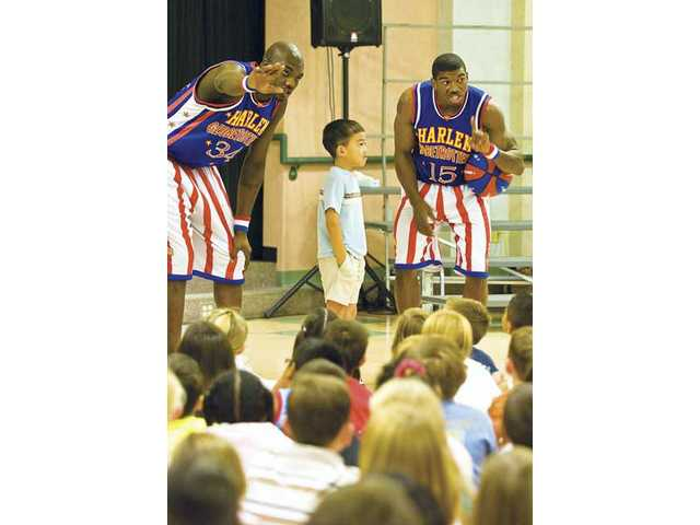 "Big Easy Lofton (34), North Park Elementary third-grader Jacob Chen and Buckets Blakes (15) talk about the ""C"" in the CHEER Program during a presentation by the Harlem Globetrotters on Wednesday at North Park."