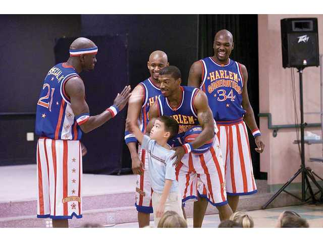 Jacob Chen exchanges high-fives with the Harlem Globetrotters, who visited North Park Elementary School on Tuesday.