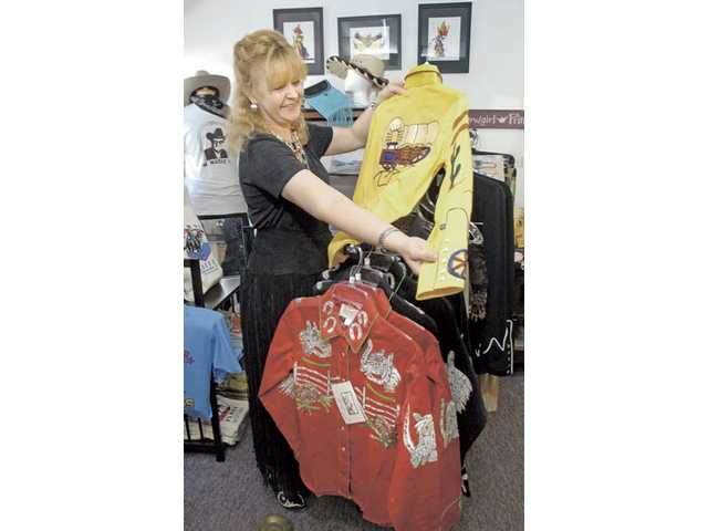 Out West owner Bobbi Jean Bell displays western designer shirts by Rockmount Ranch Wear at her Newhall store on Tuesday.