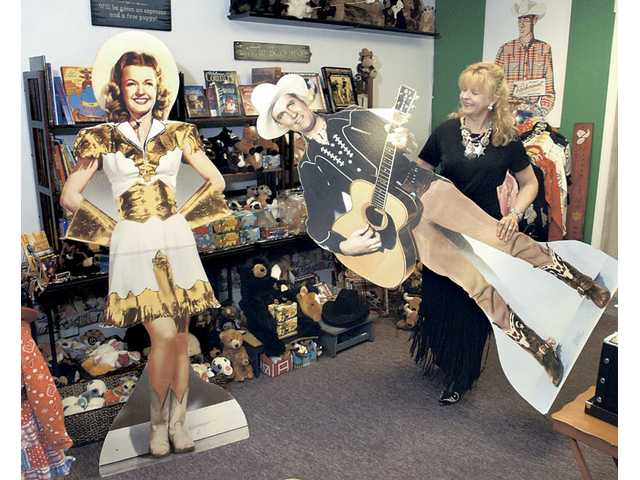OutWest owner Bobbi Jean Bell moves life-sized cutouts of Dale Evans and Gene Autry as she dresses the showroom of her Newhall store in preperation for the grand opening on Thursday.
