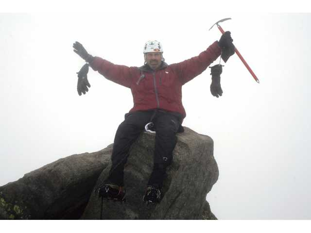 "Pfeffer throws his arms up in triumph after making it to the summit of Gannett Peak during the adventure. Upon reflection, Pfeffer called the trip ""the best week ever"" and appreciated the quality time spent with his daughter, as well as making it through difficult weather and terrain."
