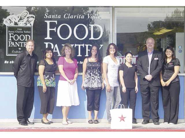 Macy's Valenica Vice President Robert Sleigh (left) and Macy's Valencia associates visit the SCV Food Pantry after raising $3,569.60 to benefit the Pantry.