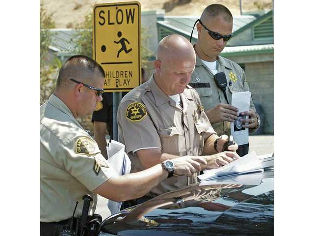 Santa Clarita sheriff's deputies set up their command post at the the family visitor center parking lot at Pitchess Detention Center as they search for an escaped prisoner from the facility in Castaic on Thursday.