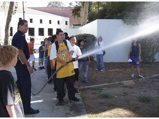 Los Angeles County Fire Dept. Capt. George Cruz assists students at the SCV Boys & Girls Club in Newhall with an impromptu fire hose drill Wednesday afternoon. The firefighters showed up for an annual inspection of the B&G Clubhouse and attracted the attention of the club's youth. Firefighters responded by dragging out the fire truck's hose and giving children instruction on how to handle a fire hose.