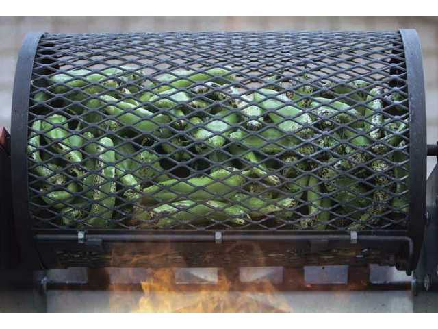 The Hatch chiles are roasted in a steel, cage-like drum and spun over open flames for about three minutes before they are ready to be boxed.