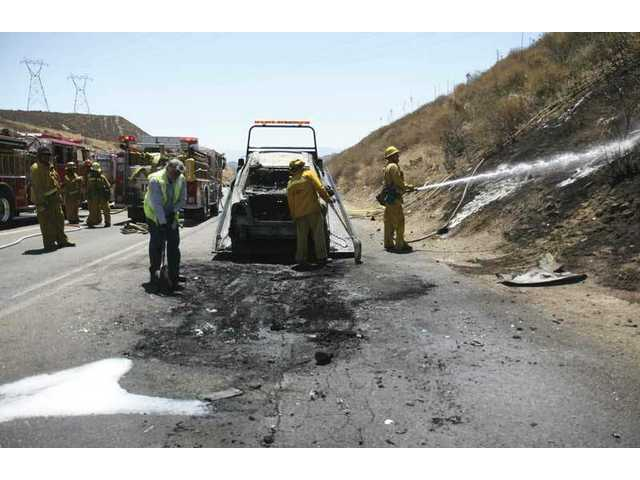 A burned car, cause of a brushfire on the southbound I-5 freeway, is taken away Thursday afternoon as fire crews mop up. The fire caused lane closures which backed up traffic for about an hour.