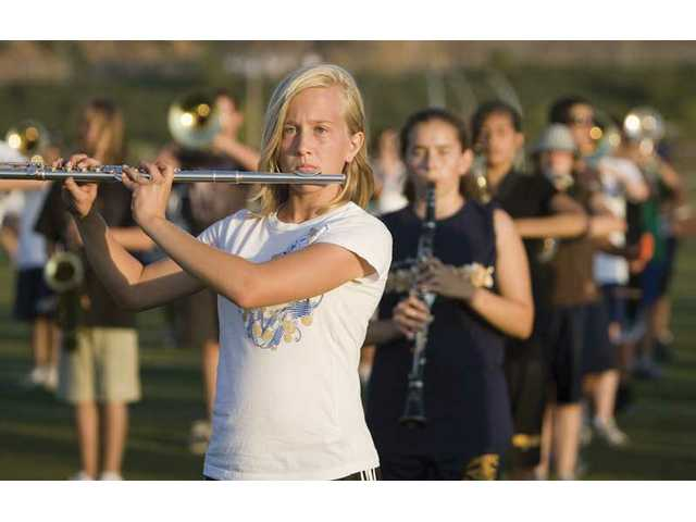 Coulette Green, with flute ready, concentrates during marching band practice at West Ranch on Thursday evening.